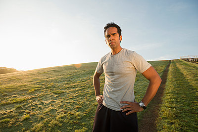 Mixed race runner standing in field - p555m1480032 by Mark Edward Atkinson/Tracey Lee
