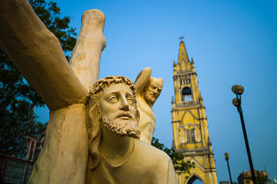 Detail of Jesus statue with Lieu De Parish Church in the background in Lieu De Town - p934m1022199 by Sebastien Loffler