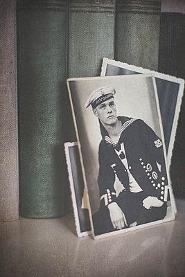 Stapel alter Fotos eines jungen Marinesoldaten im Bücherregal - p946m938937 von Maren Becker