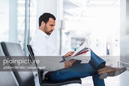 Businessman reading a newspaper in waiting hall - p300m1587364 von Daniel Ingold