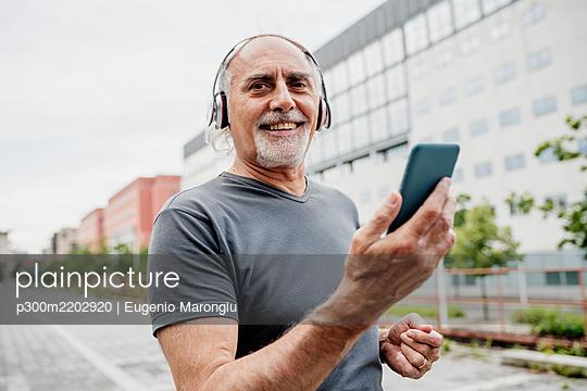 Smiling senior man wearing headphones using smart phone while standing in city - p300m2202920 by Eugenio Marongiu