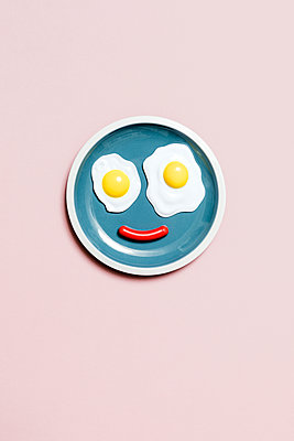 Smiling face on plate made with fried eggs and sausage - p1094m1467627 by Patrick Strattner