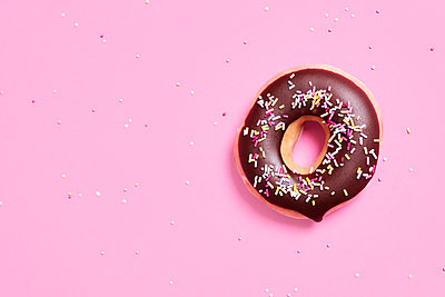 Overhead view of chocolate donut with sprinkles on pink background - p1166m2025503 by Cavan Images