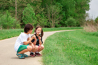 two smiling children kneel down together to blow dandelion seeds - p1166m2261270 by Cavan Images