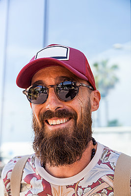 Smiling mature man with beard, red basecap and sunglasses - p300m2155817 by Tom Chance
