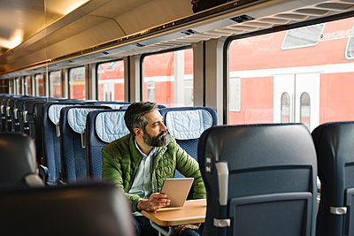 Man sitting in train holding tablet - p300m2188149 by Hernandez and Sorokina