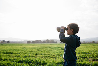 Boy looking through binoculars at agricultural field during sunny day - p300m2275592 by Josep Rovirosa