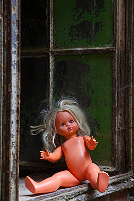 Doll sitting on a window sill - p3300341 by Harald Braun