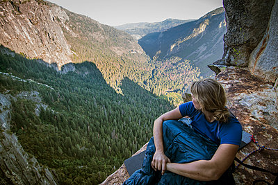 Woman sitting in sleeping bag on Dano Ledge, Yosemite Valley, Yosemite National Park, California, USA - p343m1554849 by Suzanne Stroeer