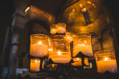 Lit candles and artwork in a cathedral; Italy - p442m2113657 by Diana Duzbayeva