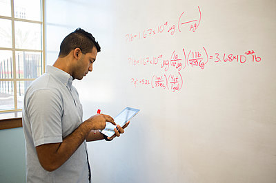 Asian businessman using digital tablet at whiteboard - p555m1412934 by Kevin Dodge