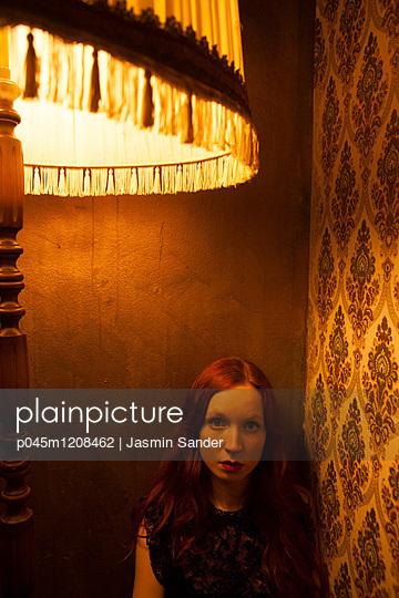 Frau sitzt in Ecke - p045m1208462 von Jasmin Sander