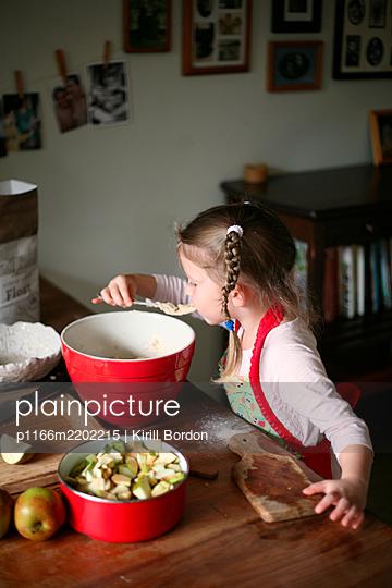 Girl tasting dough, Vancouver, British Columbia, Canada - p1166m2202215 by Kirill Bordon