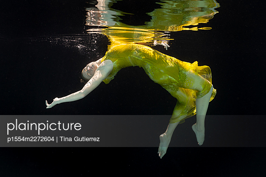 Woman in yellow dress under water - p1554m2272604 by Tina Gutierrez