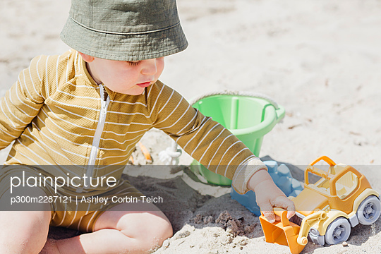 USA, California, Los Angeles. Father and toddler son holding hands on beach. Boy carrying bucket of sand toys. - p300m2287121 von Ashley Corbin-Teich