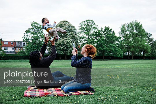 Mother photographing man playing with son at park - p300m2287205 by Angel Santana Garcia