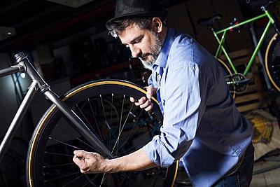 Man working on bicycle in workshop - p300m1563308 by Josep Suria