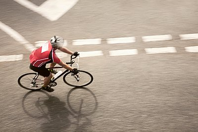 Overhead view of cyclist speeding on urban road in racing cycle race - p429m1118447f by Seb Oliver