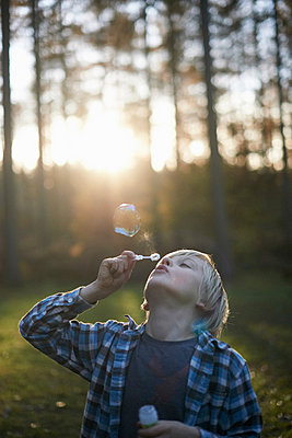 Boy blowing bubbles in forest - p429m803645f by Peter Mason