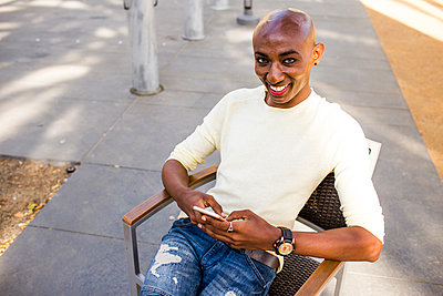 Smiling gay Black man texting in chair outdoors - p555m1304610 by Adam Hester