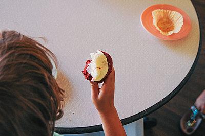 Teenage boy eating cupcake - p555m1409233 by Shestock