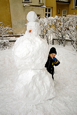 Boy hiding behind Snowman - p8474815 by Henrik Witt