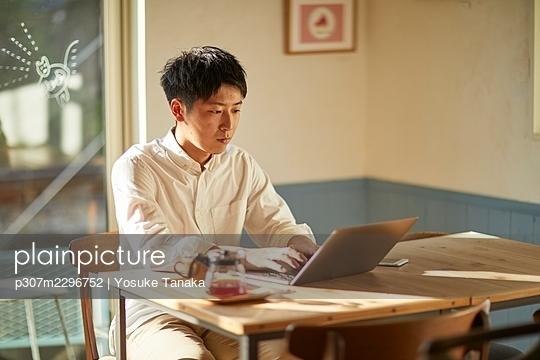Young Japanese man at a cafe - p307m2296752 by Yosuke Tanaka
