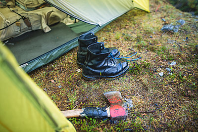 Boots and hatchet by tent - p1427m2169343 by Oleksii Karamanov