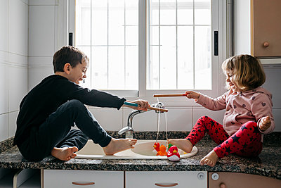 Boy and his little sister fishing rubber ducks in kitchen sink - p300m2188770 by Josep Rovirosa