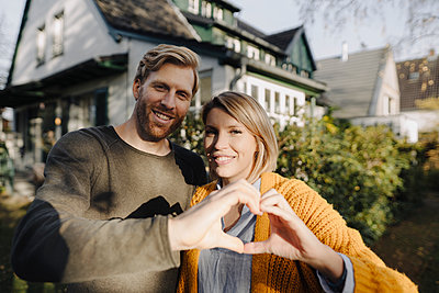 Portrait of smiling couple standing in front of their home shaping a heart with their hands - p300m2205493 by Kniel Synnatzschke