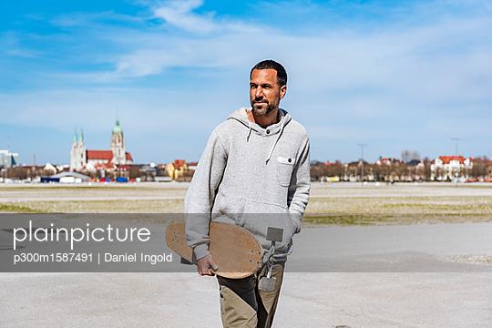 Man carrying longboard outdoors - p300m1587491 von Daniel Ingold