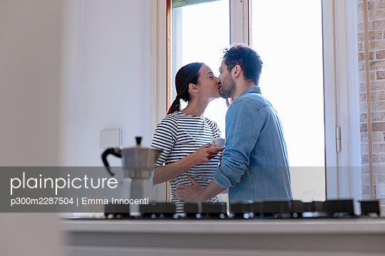 Couple kissing by window in kitchen at home - p300m2287504 by Emma Innocenti