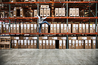 A warehouse worker trying to climb a rack of products in a distribution warehouse. - p1100m2002271 by Mint Images