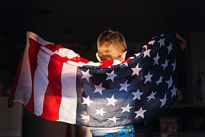 Child on his back with the American flag. 4th of July Celebration - p1166m2190920 by Cavan Images
