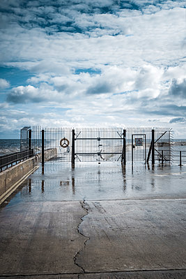 Fence and gate stopping access to a pier at the seaside with rough seas and high waves - p1302m1559628 by Richard Nixon