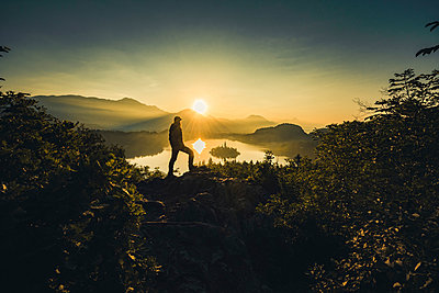 Person watching an early morning sunrise at Lake Bled - p1455m2043701 by Ingmar Wein