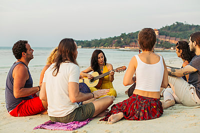 Thailand, Koh Phangan, group of people sitting on a beach with guitar - p300m1568320 by Mosuno Media
