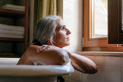 Portrait of pensive woman in bathtub looking out of window - p300m2070141 by Kniel Synnatzschke