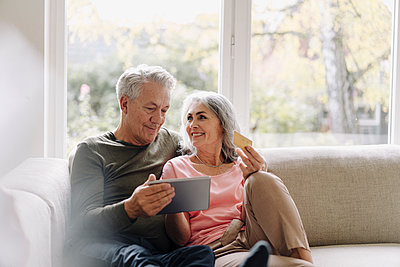 Happy senior couple relaxing on couch at home using tablet for online shopping - p300m2154983 by Gustafsson