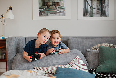 Boys playing video games together - p312m1407655 by Lisa Wikstrand