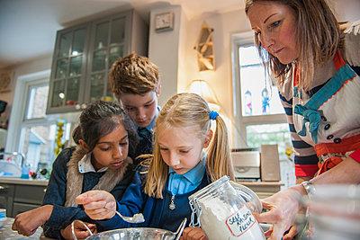 Childminder and children baking - p429m1469303 by G. Mazzarini