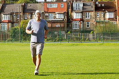 Older man jogging outdoors - p429m757578f by Elke Meitzel