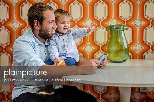 Smiling son gesturing while sitting on table by father at home - p300m2273933 by Javier De La Torre Sebastian