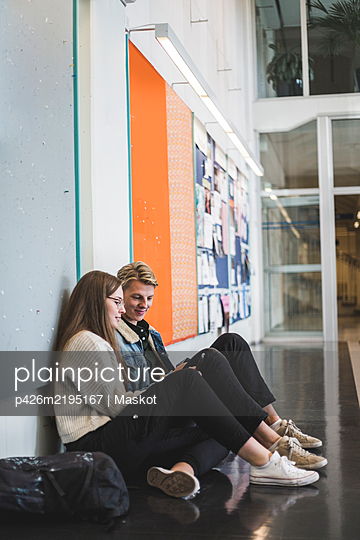 Young man sitting with female friend in corridor of university - p426m2195167 by Maskot