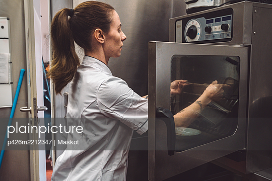 Side view of female chef putting dish in oven at commercial kitchen - p426m2212347 by Maskot
