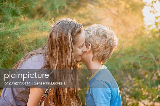 Boy and girl kneeling in a garden, whispering in each others ear. - p429m2190414 by Senserini Lucrezia