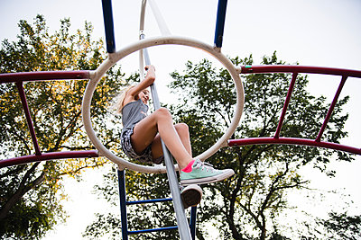 Low angle view of girl climbing on monkey bars against sky - p1166m1524523 by Cavan Images