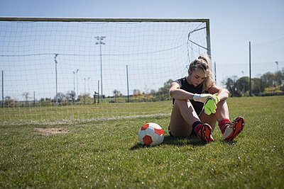 Tired soccer player sitting on field - p1315m1484430 by Wavebreak