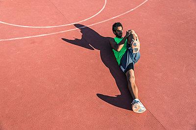 Young basketball player stretching leg - p300m1580738 by Francesco Morandini