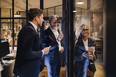 Smiling businesswoman and two businessmen working on drawing on glass pane in office - p300m2156014 by Gustafsson